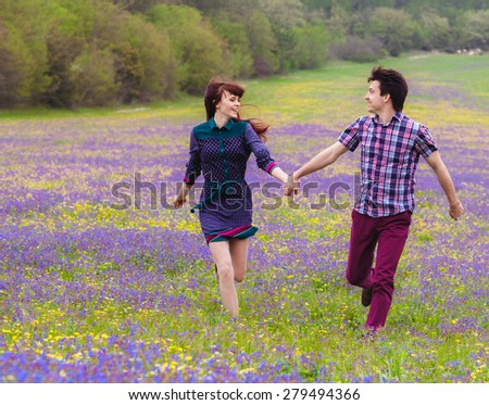 Young loving couple walking on spring meadow - stock photo