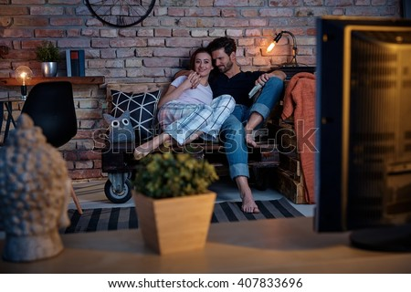 Young loving couple watching tv at home, embracing. - stock photo