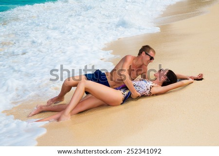 young loving happy  couple on tropical beach, lying on the sand - stock photo