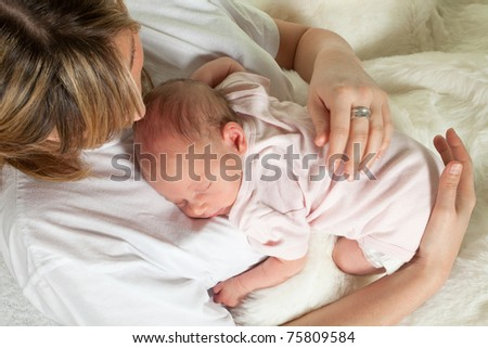 Young loving mother watching her sleeping 18 days old baby - stock photo