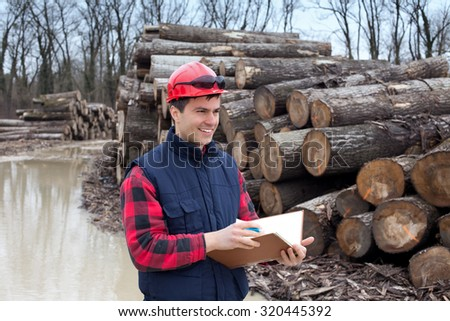 Young lumber engineer standing with notebook in front of cut trunk stock  - stock photo