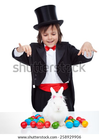 Young magician boy performing an easter trick - conjuring a white rabbit with colorful eggs, isolated
