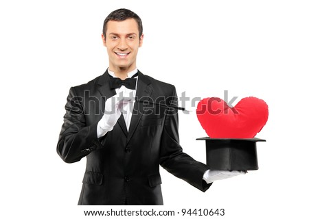 Young magician holding a magic wand and top hat with a red heart shaped pillow in it isolated on white background - stock photo
