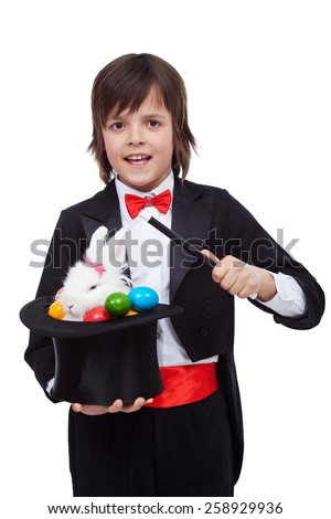 Young magician performing an easter trick - pulling a white rabbit and colorful eggs from the hat - stock photo