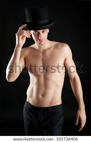 Young magician shirtless with cylinder against black background. - stock photo