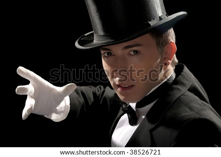 young magician with high hat on black background - stock photo