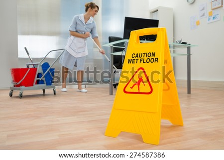 Young Maid Cleaning Floor With Mop In Office - stock photo