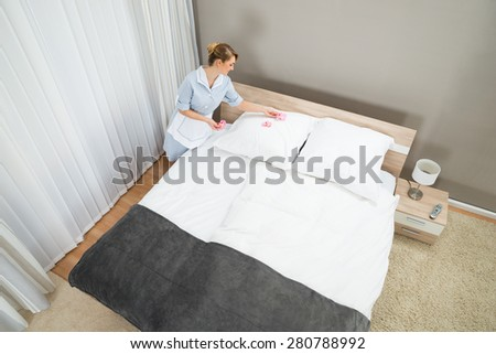 Young Maid Decorating Bedroom With Petals Of Hotel Room