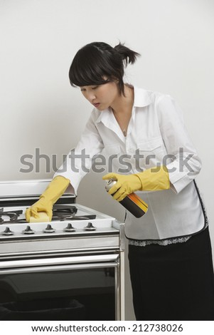 Young maidservant cleaning stove against gray background - stock photo