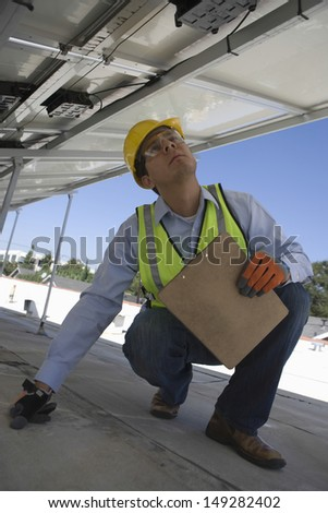 Young maintenance worker inspecting solar panels on rooftop - stock photo