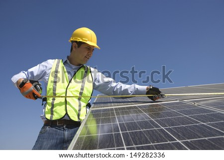 Young maintenance worker measuring solar cells on rooftop - stock photo