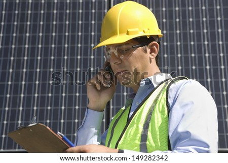 Young maintenance worker using cell phone while looking at clipboard near solar panels - stock photo