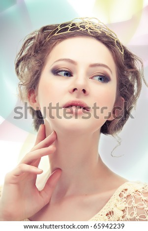 Young majestic woman in a diadem of gold on abstract background.