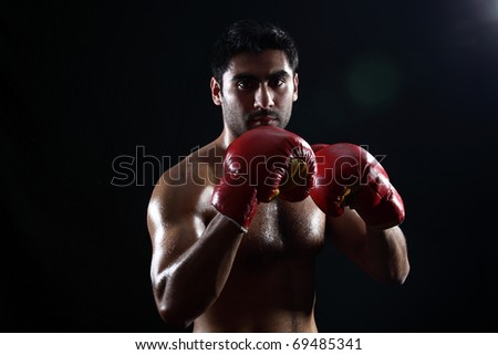 young make boxer posing on black geniune lens flare on the background - stock photo