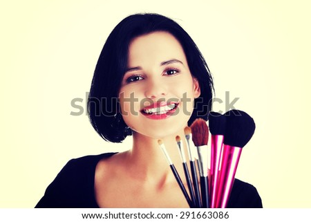 Young make-up artist woman holding brushes - stock photo