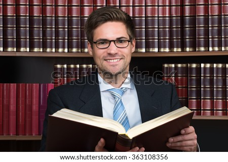 Young male advocate reading legal book at courtroom - stock photo