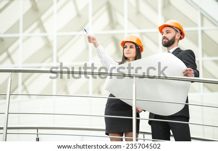 Young male and female architect in the modern office. - stock photo