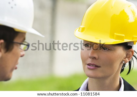 Young male and female managers working together in an industrial situation - stock photo