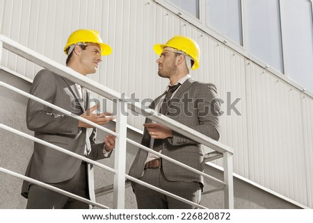 Young male architect discussing on stairway against building