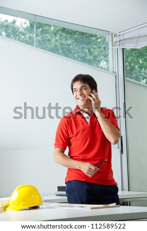 Young male architect smiling while answering phone call