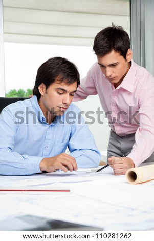 Young male architects working on blueprint together in office - stock photo