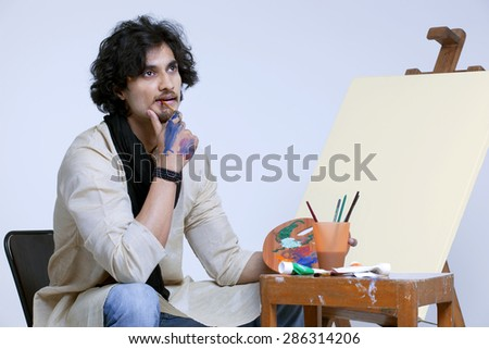 Young male artist contemplating near easel against colored background - stock photo