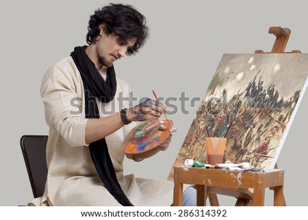 Young male artist mixing colors while painting - stock photo