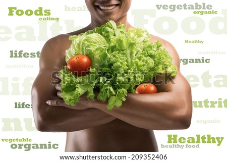 Young male athlete holding  fresh vegetables and showing his muscle  - stock photo
