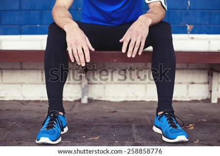 young male athlete resting on the bench - stock photo