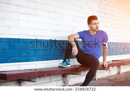 young male athlete sitting on the bench (intentional sun glare) - stock photo