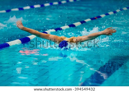 young male athlete swimmer swims at competitions butterfly - stock photo
