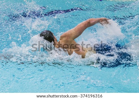 young male athlete swimming freestyle in pool during competition - stock photo
