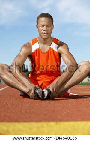 Young male athlete warming up on racing track - stock photo