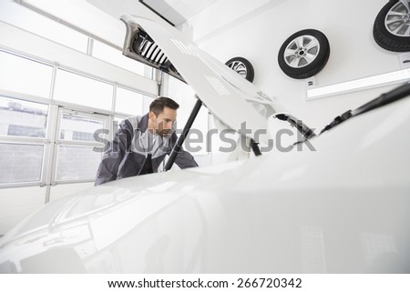 Young male automobile mechanic examining car engine in repair shop - stock photo
