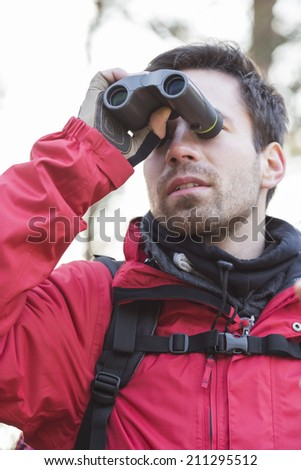 Young male backpacker using binoculars in forest - stock photo