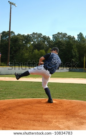 Young male baseball player winds up for the pitch.  Navy and white uniform.  Blue skies and baseball field.