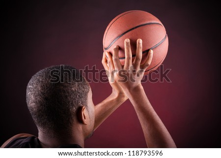 Young male basketball player against black background - stock photo