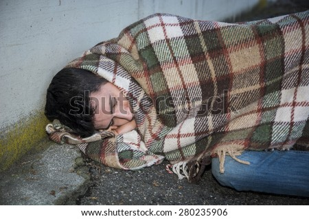 Young male beggar sleeping on city sidewalk with blanket on his shoulders - stock photo