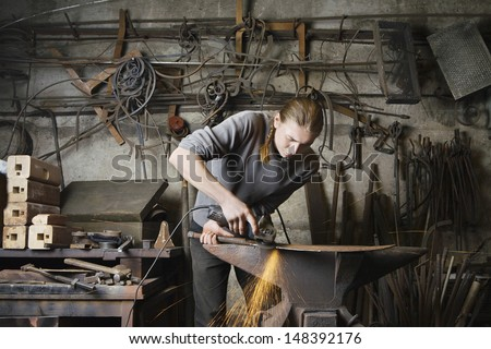 Young male blacksmith working in workshop - stock photo