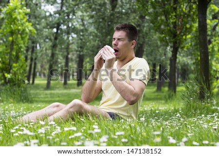 Young male blowing his nose outdoors, having problem with allergy