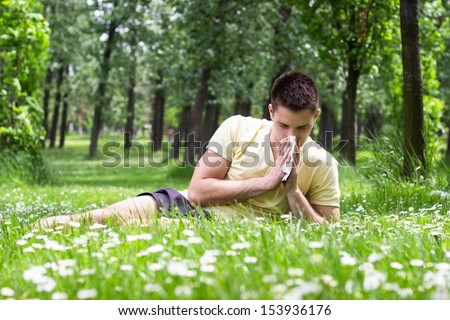 Young male blowing his nose outdoors, sneezing among flowers, having problem with allergy