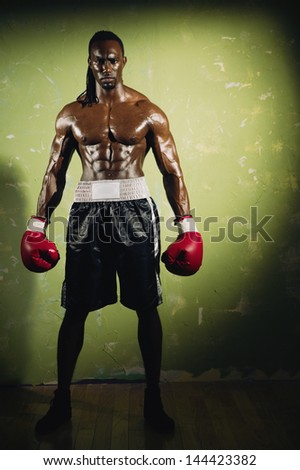 Young male boxer standing in spotlight - stock photo