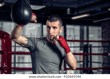 Young Male boxer using a punching bag in gym. Boxer hitting punching speed bag in gym, head and shoulders. Athlete with red boxing bandages. - stock photo