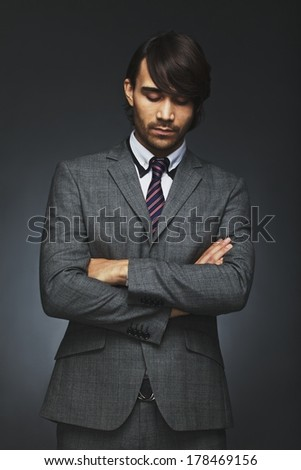 Young male business executive with his arms crossed looking down in thought. Thoughtful businessman in suit standing against black background. Male model in suit looking pensive. - stock photo