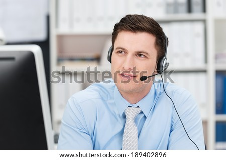 Young male call centre operator sitting wearing a headset sitting listening to a conversation with a pensive thoughtful expression
