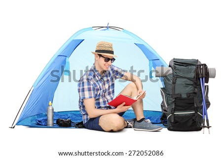 Young male camper reading a book seated on the ground with a blue tent behind him and a large backpack beside him isolated on white background - stock photo