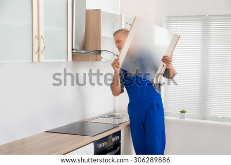 Young Male Carpenter Making Furniture In Kitchen Room - stock photo