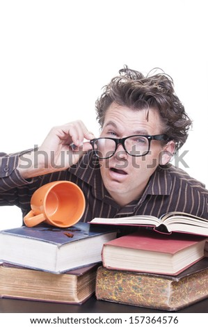 Young male Caucasian student with messy hair wakes up after all night bout to stay awake studying with spilled coffee on pile of books on white background with text copy space - stock photo