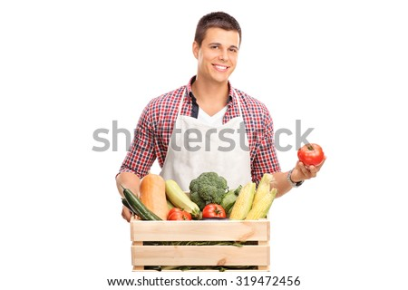 Young male chef in white apron posing with a crate full of fresh vegetables and holding a single tomato in his hand isolated on white background
