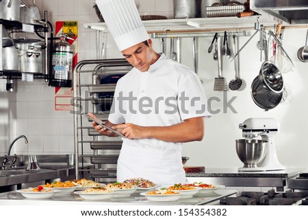 Young male chef using digital tablet with pasta dishes at kitchen counter - stock photo